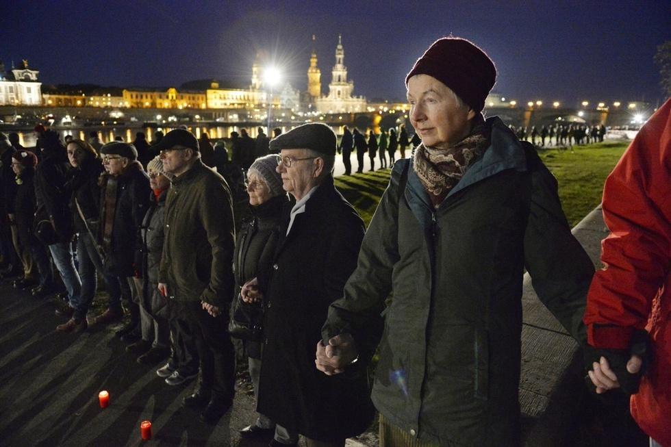 第2次大戦中の空襲による犠牲者を悼み、手をつないで「人間の鎖」をつくる人たち。シリアなどから多くの難民が流れ込むドイツで、出身や人種、宗教にかかわらず手を取り助け合う寛容さを訴えていた=ドイツ・ドレスデン(撮影・伊藤智昭、共同)