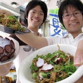 被災地支援で考案したたこそばめしを手にする流通科学大生=神戸市長田区久保町6