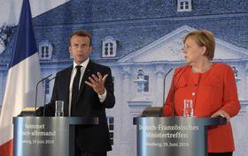 記者会見で発言するフランスのマクロン大統領(左)とドイツのメルケル首相=19日、ベルリン近郊(AP=共同)