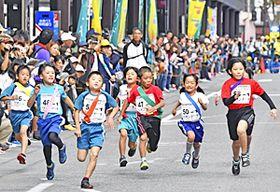 中心市街地を元気に駆け抜ける子どもたち=14日午前、会津若松市・神明通り
