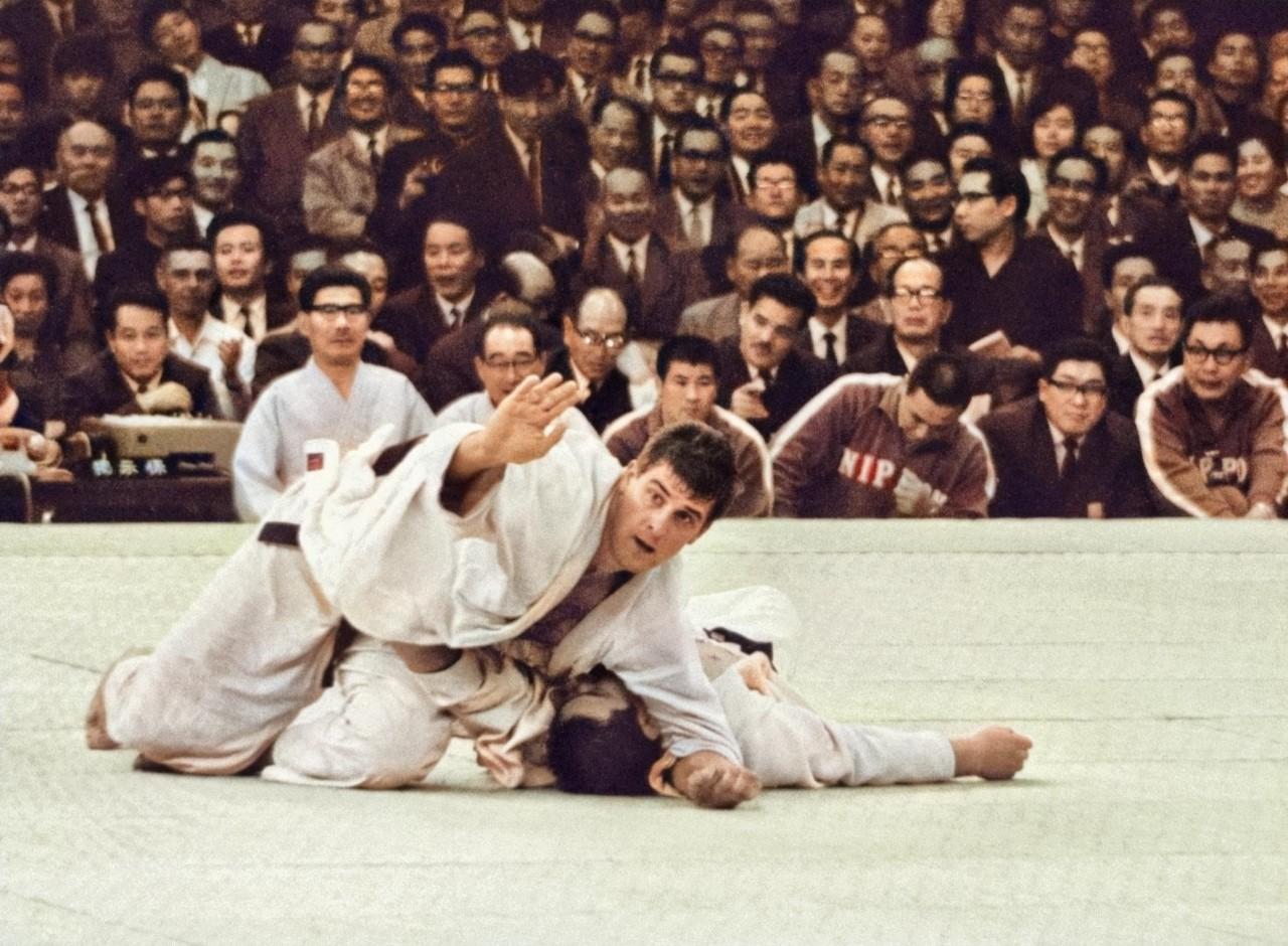 1964年10月23日、柔道無差別級決勝で神永昭夫選手(下)をけさ固めで破り優勝したオランダのヘーシンク選手。喜んで畳に駆け上がろうとした青年を手で制した
