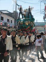 獅子をかたどった巨大な曳山を綱で引く曳子たち=佐賀県唐津市