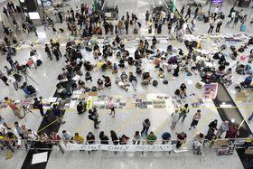 香港国際空港の到着ゲート前で座り込みを続けるデモ隊ら=14日(共同)