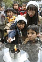 「1.17希望の灯り」の分灯で、ろうそくに火を移す子ども=12日午後、神戸市の東遊園地