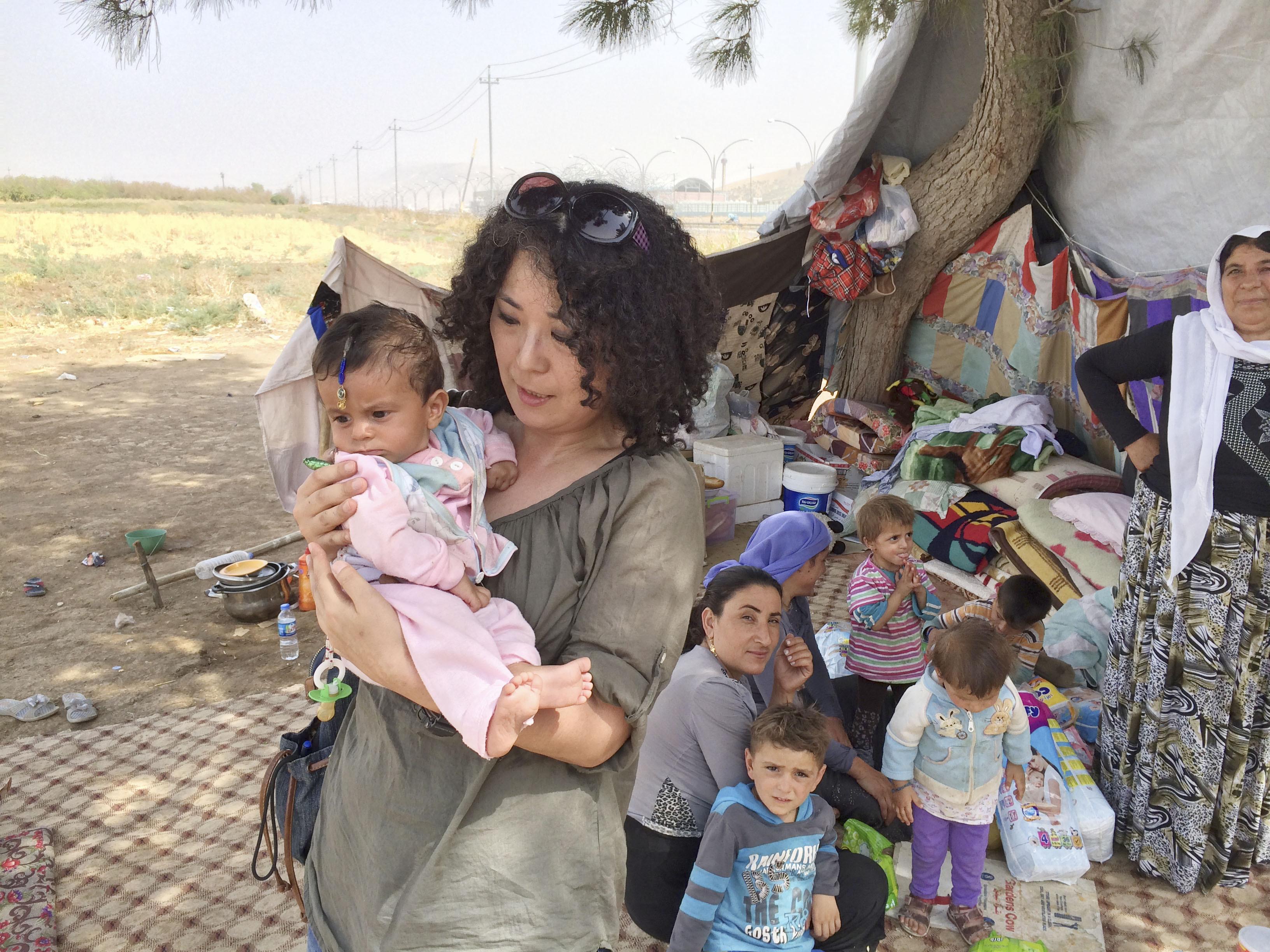 過激派「イスラム国」の攻撃を受け、避難民となったイラクのクルド民族少数派ヤジド教徒の家族を支援する高遠菜穂子=2014年8月、イラク北部クルド自治区(本人提供・共同)(敬称略)