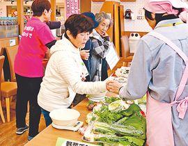 野菜の重さを量る買い物客(中央)