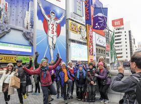大阪・ミナミの名所、グリコの看板前でポーズを取る訪日観光客ら=4月