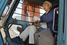 自らショベルカーに乗り込み、用水路建設作業に当たる中村哲医師。「重機を操るのは楽しい」と話していた=2014年11月、アフガニスタン(撮影・中原興平)