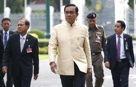 閣議に向かうタイのプラユット首相(中央)=11日、バンコク(AP=共同)