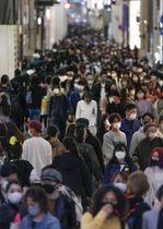 大阪・ミナミを行き交う人たち。大阪府では新型コロナウイルスの新規感染者が6日連続で千人を超えた=18日午後5時36分