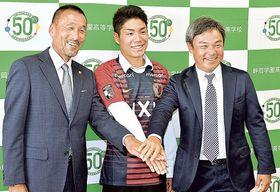 鹿島のユニホームに初めて袖を通し、笑顔がはじける静岡学園高の松村(中央)。左は鹿島の椎本スカウト担当部長、右は静岡学園高の川口監督=静岡学園高