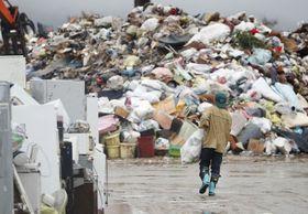 雨が降る中、災害ごみを片付ける男性=22日午後、宮城県丸森町