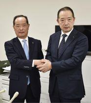 高島屋の次期社長に決まり、木本茂社長(左)と握手する村田善郎常務=15日午後、東京都千代田区