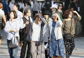 多くの地点で真夏日となった5月30日、手で日差しを避けて歩く人たち=東京都内