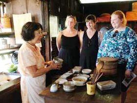 米ハワイ島の「コナ・コーヒー・リビングヒストリー・ファーム」の台所で昔の生活ぶりを説明するポーリーン・ヒラタさん(左)=3月(共同)