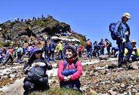 青空の下、山頂で疲れを癒やす登山客=20日午前、安達太良山