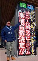 秋田市役所正面玄関に設置された事前キャンプ決定を祝う看板とセタレキ・タワケ氏