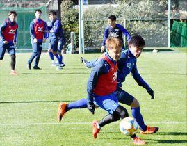 サイドで激しくボールを競り合うMF野村(手前)とDF久米=高知市の春野総合運動公園球技場
