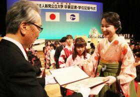 公文学長(左)から卒業証書を受け取る卒業生