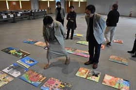 子どもたちの力作を並べ、意見し合う審査員たち=青森市の東奥日報社本社