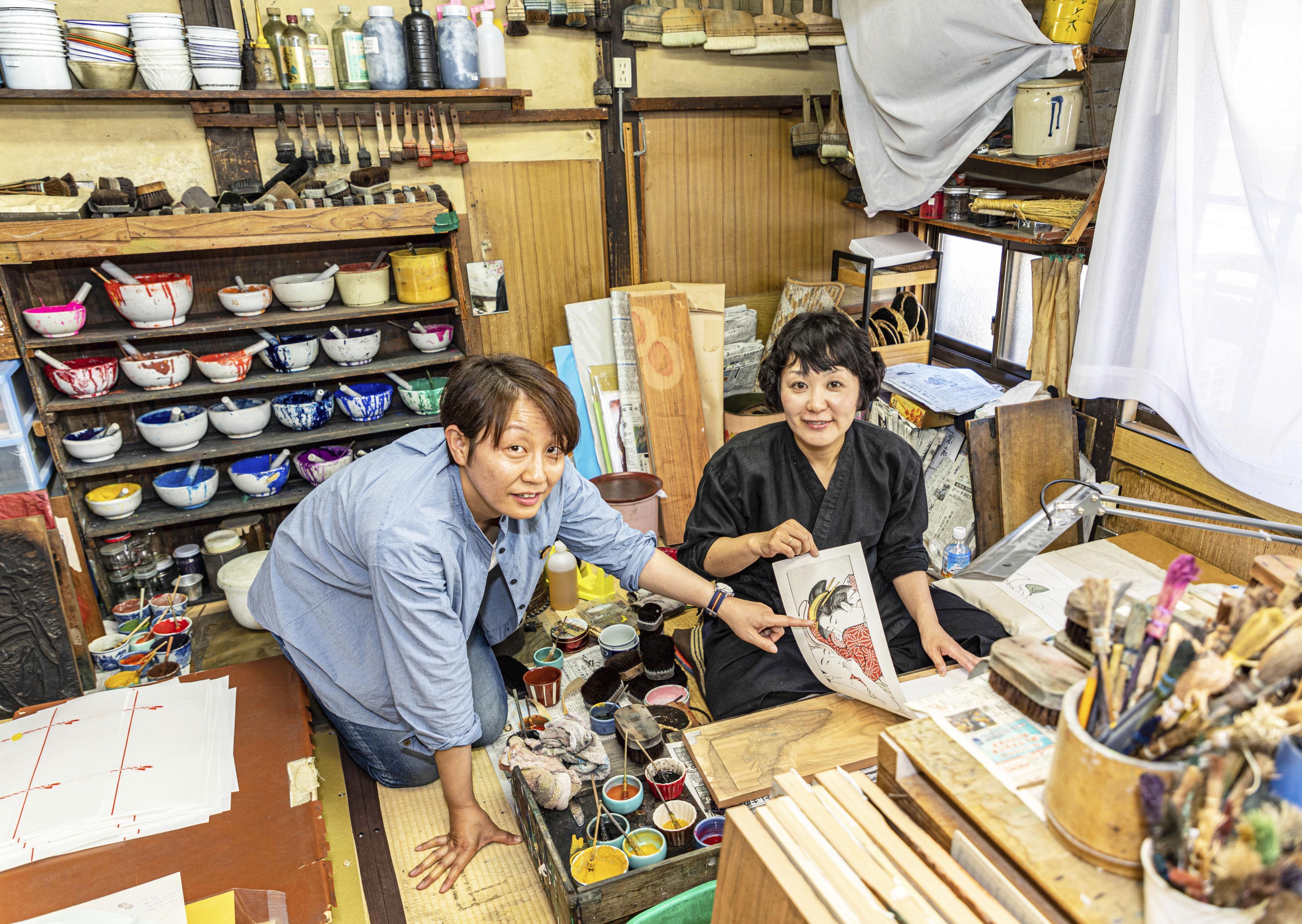 京都市東山区の工房で、「お嬢さんと手代」を摺り上げた平井恭子(右)と石上亜希