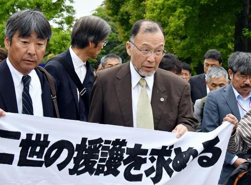 第1回口頭弁論のため、原告や支援者とともに広島地裁へ入る在間秀和さん(中央)。「放射線の影響に関する真実は隠されてきたのではないか。過去の問題ではなく現在の問題として、この訴訟を位置付けたい」と語気を強める=5月9日、広島市中区(撮影・西詰真吾)