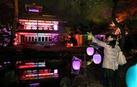 光の色を変えながら、夜の庭園に浮かび上がった旧三井家下鴨別邸(14日午後6時5分、京都市左京区)