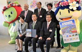 記念切手を受け取った阿部知事(手前中央)と日本郵便信越支社の関係者ら=21日、松本市