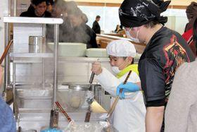 サポートを受けながらラーメンの湯切りに挑戦する子どもたち=伊奈町小室の日本薬科大学