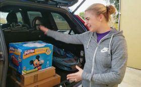駐車中の車に荷物を配達する米アマゾン・コムの新しいサービスを体験した女性(同社提供・共同)