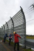 小雨交じりの曇天の下、防雪柵の設置を手際よく進める作業員=14日午前11時15分ごろ、青森市宮田