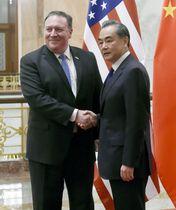 会談を前に握手するポンペオ米国務長官(左)と中国の王毅国務委員兼外相=14日、北京の人民大会堂(共同)