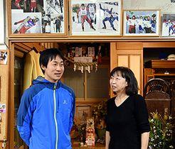 永井秀昭選手の2大会連続の五輪内定の報を受け、過去の写真の前で喜びに浸る長兄陽一さん(左)と母綾子さん=22日、八幡平市