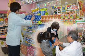 インフルエンザの流行期に入り、八戸市内では感染予防の動きが広がる(写真はコラージュ。対策グッズコーナーを設置しているドラッグストアと予防接種を受ける子ども)