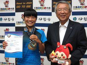 【アジアジュニア選手権でのメダルを手にする濱口さん(左)=伊勢市小俣町の市小俣総合支所で】