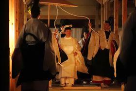 「悠紀殿供饌の儀」のため、薄明かりの中、祭服を着て大嘗宮の悠紀殿に向かわれる天皇陛下=14日午後6時35分、皇居・東御苑