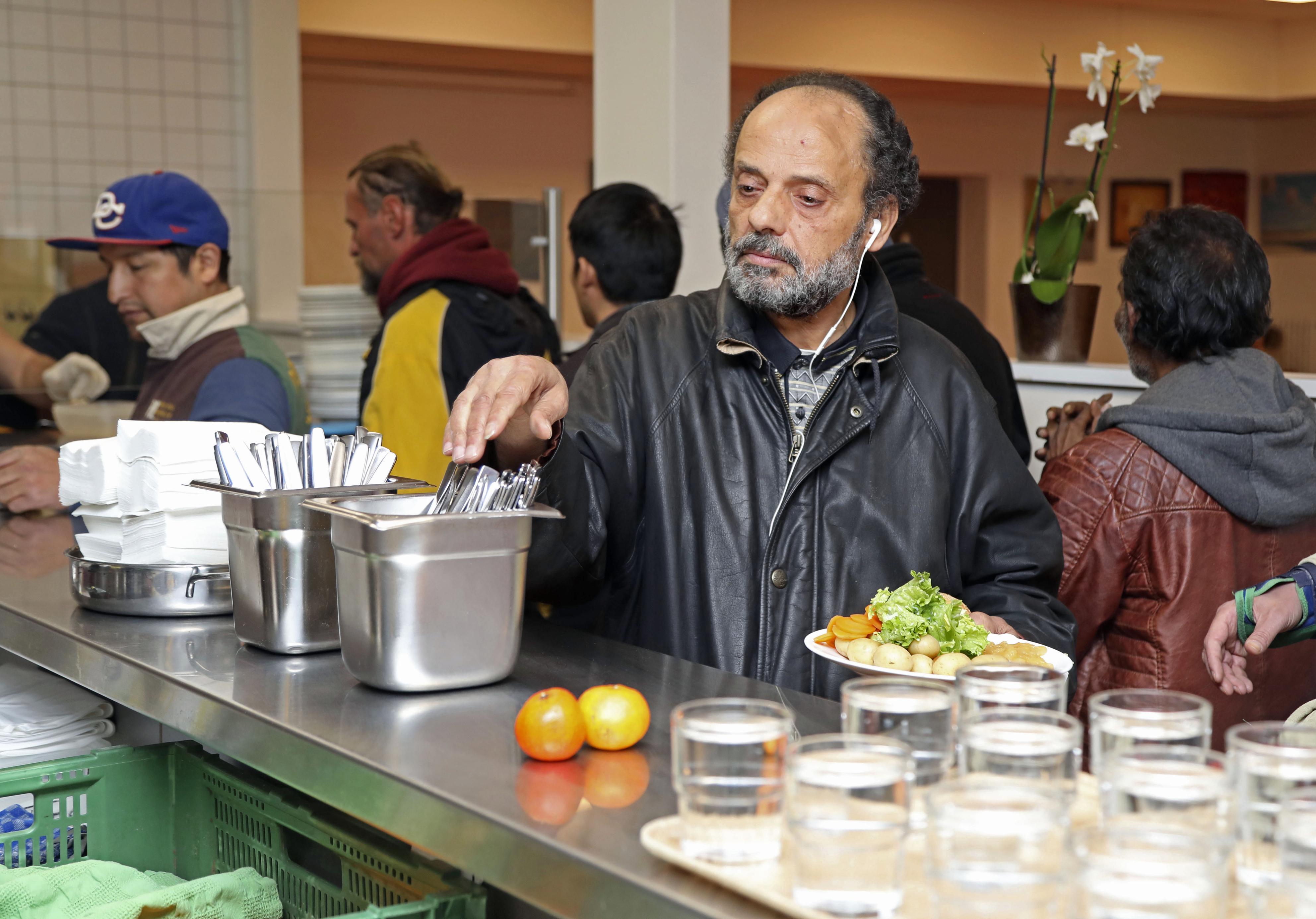 市が運営する貧困者向け無料食堂でランチの行列に並ぶサミール=10月、スイス・ジュネーブ(共同)