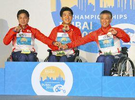 男子1500メートル(車いす)で、表彰台を独占する(左から)2位の上与那原寛和、優勝の佐藤友祈、3位の伊藤智也=ドバイで(神谷円香撮影)