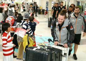 大分空港に到着し、出迎えた県民に笑顔を見せるサンウルブズの選手たち=19日午後、国東市