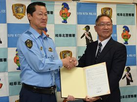 協定書に署名し、握手を交わす立石薫署長と遠藤隆司社長(右)=岐阜北署