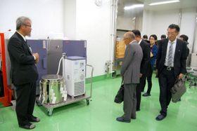 発酵タンク(手前左)を見学する出席者