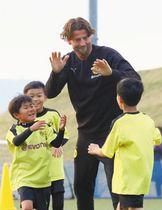 参加した児童らとハイタッチを交わすワイデンフェラーさん=蟹江町新千秋の希望の丘広場フットサルコートで