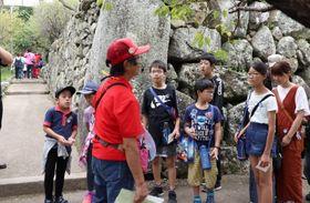 ボランティアガイドの案内を受けながら謎スポットを巡る参加者=島原城