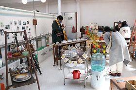 竹乃湯の浴室に並ぶ古道具を手に取る人たち