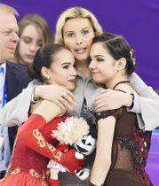 平昌冬季五輪のフィギュア女子で金メダルを獲得し、トゥトベリゼ・コーチ(中央)に祝福されるアリーナ・ザギトワ(左)と銀メダルのエフゲニア・メドベージェワ両選手=2018年2月23日、韓国・江陵(共同)