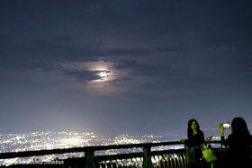 雲の切れ目から姿を見せた月=24日午後7時すぎ、徳島市の眉山山頂