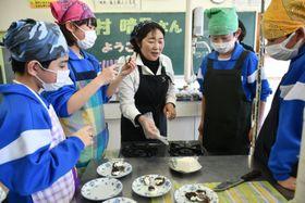 木村晴子さん(中央)から干し柿を使った料理の作り方を教わる大川目中の生徒たち