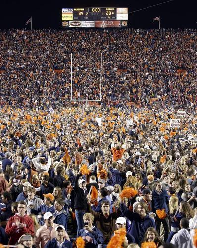 劇的な勝利に歓喜してフィールドになだれこむオーバーン大のファンら=11月30日、(AP=共同)