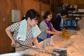 都城市の大浦酒造で蒸し上がったこうじ米を冷ます作業を体験する編集者