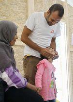 ギリシャ・レスボス島の診療所で活動する「文化の仲介者」の一人、タミム・ナガル(右上)。「イスラム国(IS)」に夫を殺された女性(左)はイラクから3人の子どもを連れて逃れてきた。娘はナガルの前では安心したような笑顔を見せる=6月